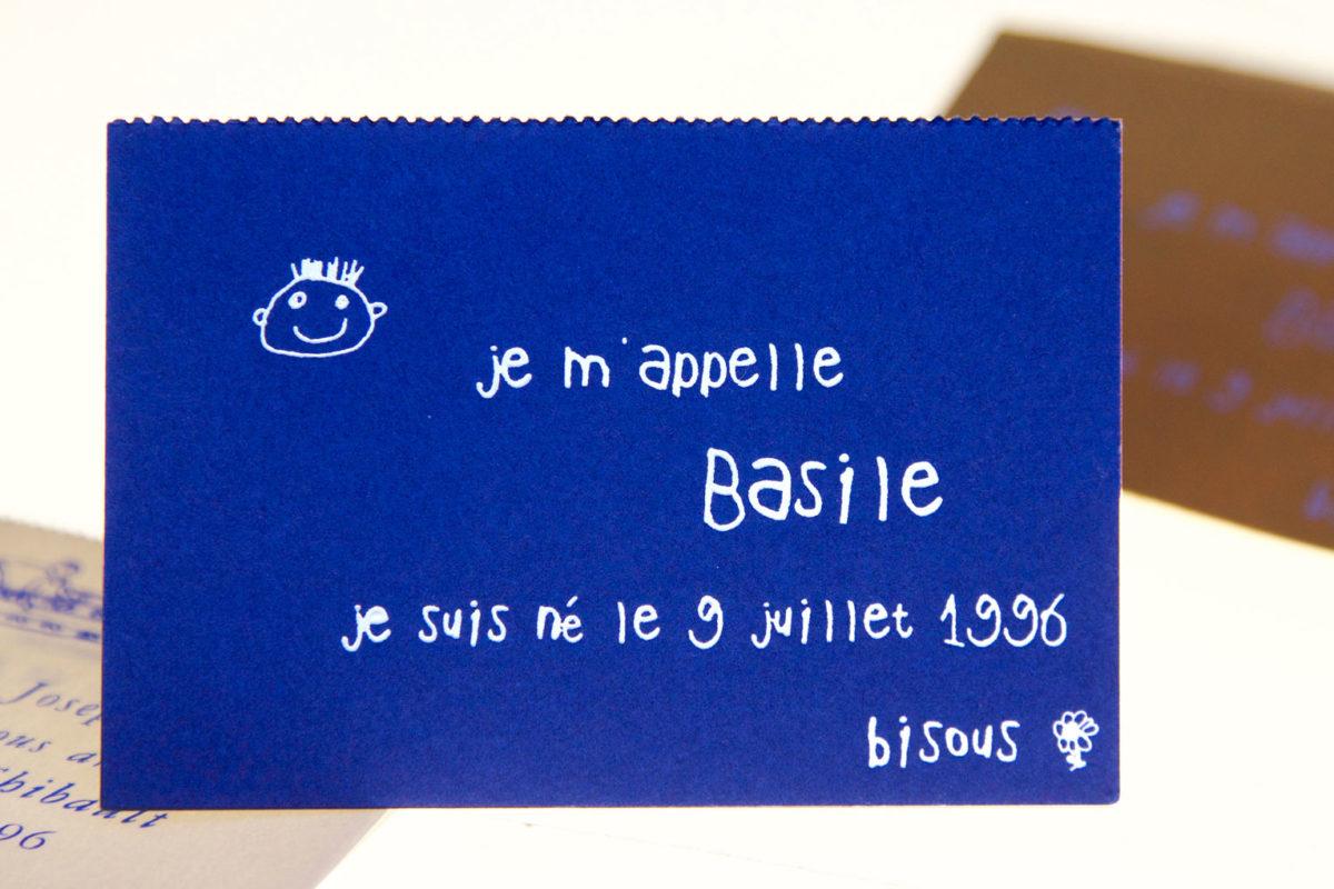 Cette photo représente le faire-part de naissance crée par Stéphane Le Sauter pour la naissance de son fils Basile en 1996, Gravure à chaud pigment blanc sur papier bleu carte-chevalet