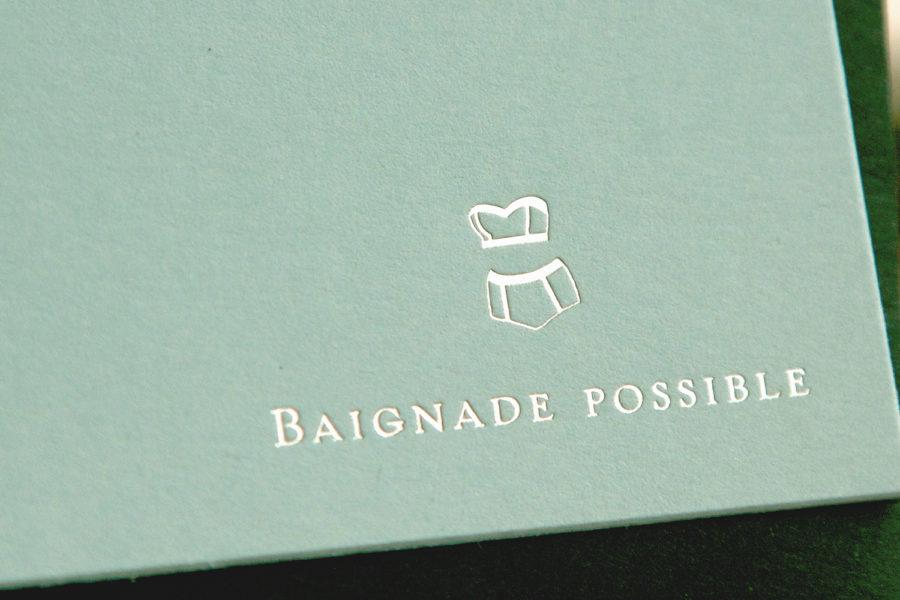 Faire-part de mariage avec un pictogramme illustrant un bikini et Baignade possible gravé or blanc sur papier pistachio par l'imprimerie Intaglio