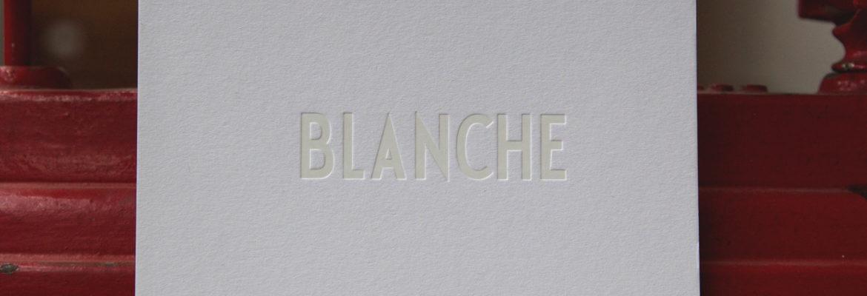 Cette photo représente un faire-part de naissance en dorure à chaud blanche sur papier blanc naturel