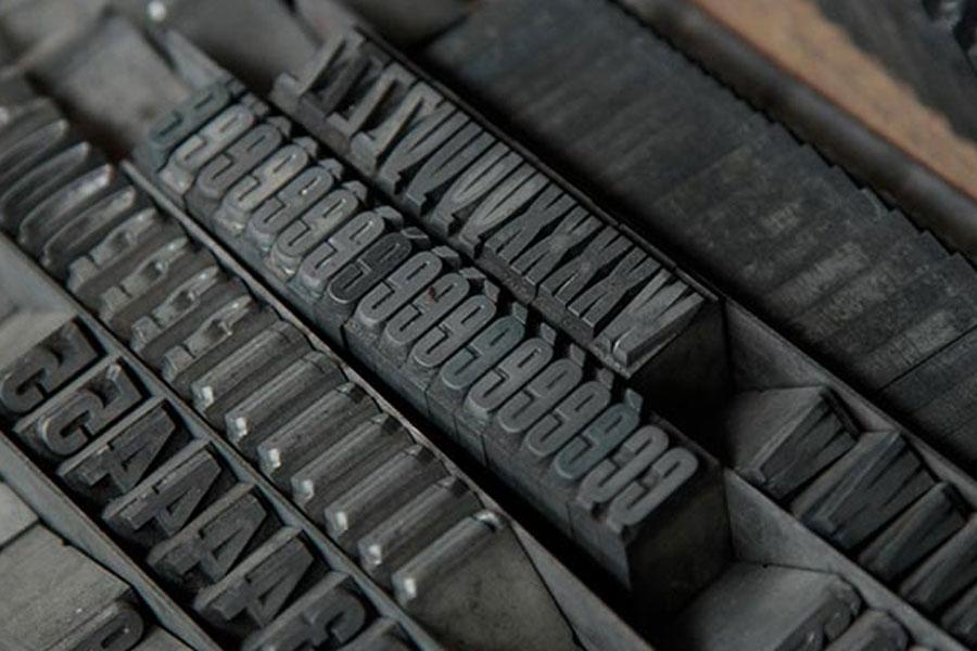 La photo représente des caractères en plomb pour l'impression de faire-part de naissance en letterpress typographie de l'atelier d'imprimerie Intaglio à Paris