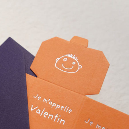 La photo représente le Faire-part naissance Cube avec la bouille de Cosimo en ggravure argent sur une carte couleur mandarine