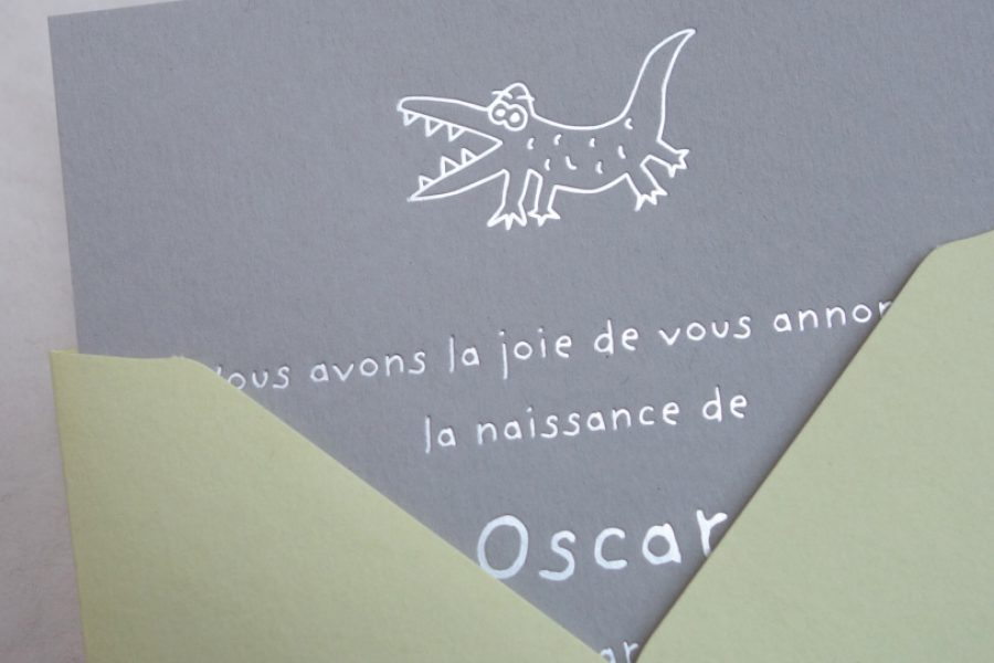 La photo représente un faire-part de naissance Toys avec l'illustration du crocodile en gravure argent sur une carte de couleur grey